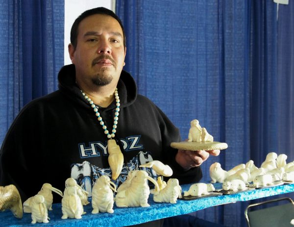 Dennis Pungowiyi shows off one of his favorite carving motifs, a mother walrus with her pup. (Zachariah Hughes/Alaska Public Media)