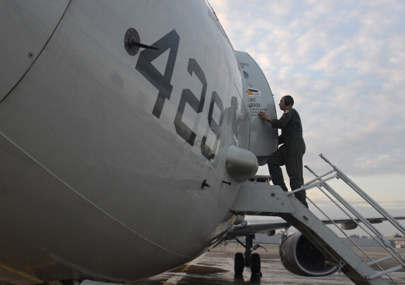 A U.S. Naval Aircrewman enters a P-8A Poseidon, military maritime surveillance aircraft, in Malaysia in 2014. (Mass Communication Specialist 2nd Class Eric A. Pastor/U.S. Navy/Getty Images)