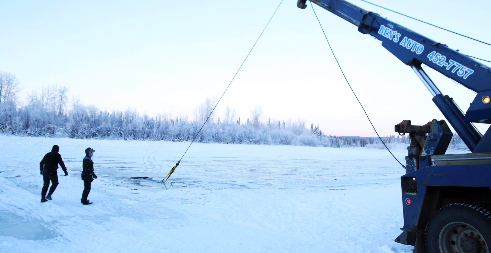 In this Dec. 19, 2014 photo, a dive crew watches the recovery of a vehicle from the icy water near the Pike's Landing Chena River Ice Bridge entrance in Fairbanks, Alaska. At least two vehicles recently sank into the Chena River on a section long used as an ice-covered shortcut between Airport Way and Chena Small Tracts Road. (Eric Engman/The Fairbanks Daily News-Miner/AP)