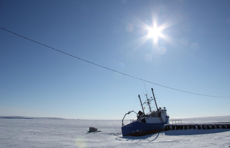 A komatik (an Inuit sled) beside a boat outside of Cambridge Bay, Nunavut. (Eilís Quinn/Eye on the Arctic)
