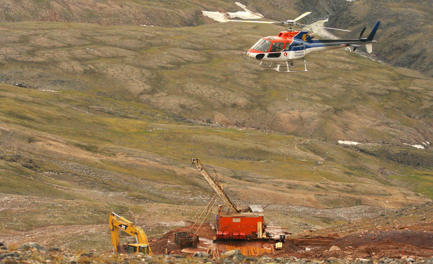 A helicopter passes over excavation equipment at the Mary River exploration camp in 2006. (Vinne Karetak/The Canadian Press)