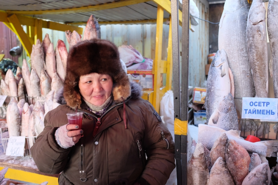A Yakut woman selling fish, vertically frozen, at a market in Yakutsk, the capital of the Sakha Republic, in Russia, and one of the coldest cities on earth. (Mia Bennett)