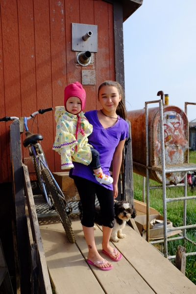 A girl, her little sister, and their pet dog in Tuktoyaktuk, Northwest Territories, Canada. (Mia Bennett)