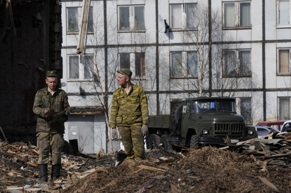 Workers tear down some of the old houses in the center of Korzunovo. (Thomas Nilsen/The Independent Barents Observer)