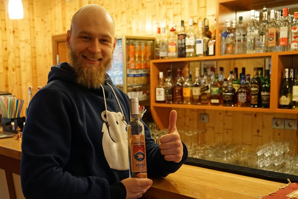 Ivan Velichenko shows a bottle of the town's own vodka named Barentsburg. (Thomas Nilsen/The Independent Barents Observer)