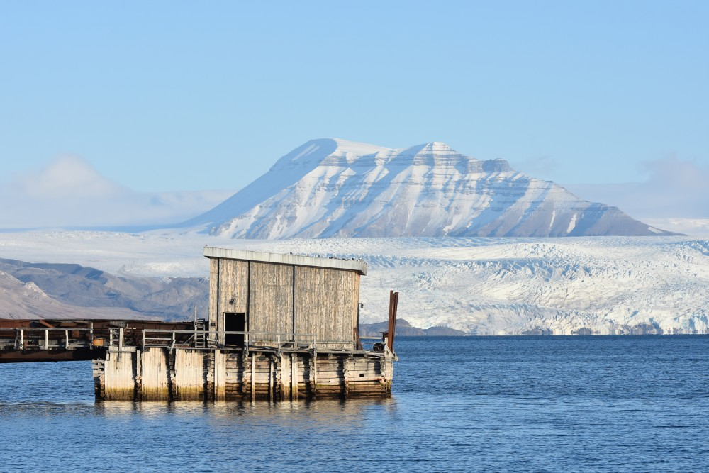 Part of the port facility in Pyramiden. The Nordenskiöld glacier across the fjord. (Thomas Nilsen/The Independent Barents Observer)