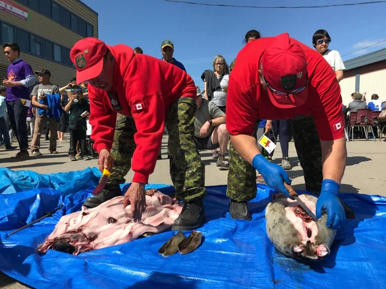 Canadian Rangers prepare seals and hand out fresh meat as part of the day's celebratory feasting. (Sara Frizzell/CBC)