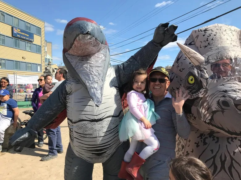 Addison Tsang introduces his granddaughter Stella to some dinosaurs who were out celebrating Nunavut Day. (Sara Frizzell/CBC)