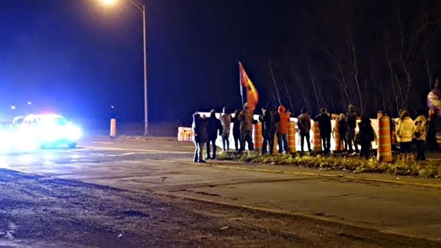 Seuls, une quarantaine de manifestants amérindiens mohawks ont bloqué pendant quelques heures l'accès au pont Honoré-Mercier sur la route 132 en direction de Montréal, mardi soir, sur leur réserve de Kahnawake, pour marquer leur opposition au déversement de huit milliards de litres d'eaux usées dans le fleuve Saint-Laurent, autorisé par la Ville de Montréal. « Sauvons notre fleuve », pouvait-on lire sur l'immense banderole qu'ils ont déployée près de la route, où ils ont aussi fait un feu et brandi des drapeaux mohawks. (Alain Béland - RC)