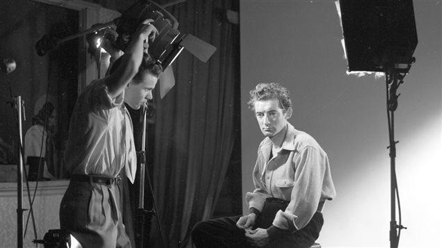 Félix Leclerc, auteur-compositeur-interprète (Sur la photo est aussi présent Gaby ajustant l'éclairage) (Vers 1951) - Ronald Desmarais/Gaby, collections BAnQ