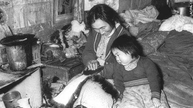 Femme expliquant la technique à un enfant : Inuits d'Ungava, Fort Harrison, Québec, 1947-48 (Richard Harrington) Crédit photo : virtualmuseum.ca