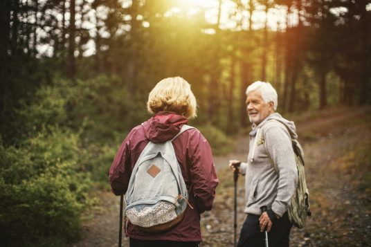 Photo of a senior couple, hiking through the forest and exploring nature