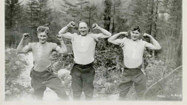 Trois membres du Corps forestier canadien en Europe. La solide réputation des robustes bûcherons canadiens a mené à la création du Corps forestier canadien en 1916. Près de 24 000 bûcherons du Canada se sont rendu en Europe à cette époque. Photo Credit: Archives George-Metcalf