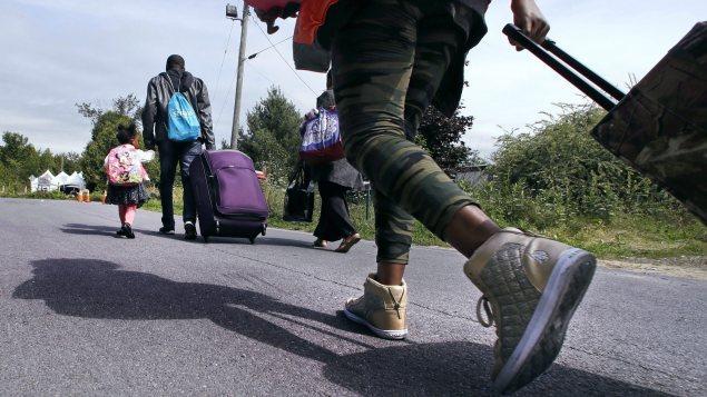 Une famille de demandeurs d'asile arrivant des États-Unis traverse la frontière canadienne cet été. - Radio-Canada