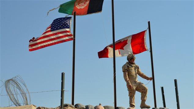 Un soldat canadien s'apprête le 11 mars 2014 à mettre le drapeau canadien en berne à la base de Zangabad, en Aghanistan, lors du retrait des forces canadiennes de Kandahar (archives).