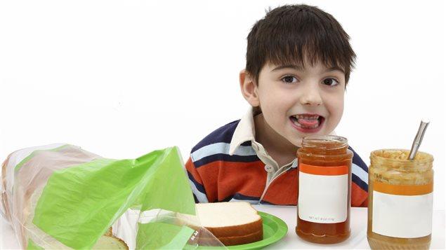 Un petit garçon s'apprête à manger du beurre d'arachide pour déjeuner. Photo Credit: iStock
