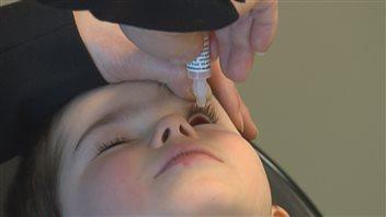 Un enfant canadien reçoit un traitement sous forme de goutte dans l'oeil gauche pour éviter la cécité. © Hema Québec