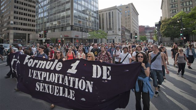 Des féministes manifestent contre la prostitution durant le Grand Prix de formule 1, au centre-ville de Montréal. Photo Credit: PC / Peter Mccabe
