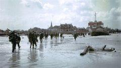 Des soldats de l'infanterie canadienne débarquent sur la plage de Juno Beach et marchent en direction de Bernières-sur-Mer. Photo : Conseil régional de Basse-Normandie/Archives nationales du Canada