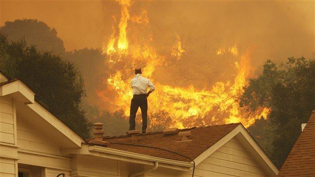 Un Canadien en 2017 regarde le feu s'approcher de sa maison. Les feux de forêt plus fréquents sont l'un des phénomènes que l'on associe au réchauffement climatique.Photo Credit: David McNew/Getty Images RCI avec La Presse canadienne et Radio-Canada