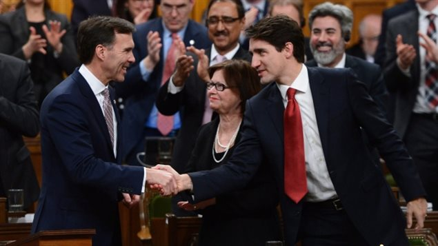 Le premier ministre Justin Trudeau, à droite, serre la main au ministre des Finances, Bill Morneau, après avoir déposé le budget fédéral à la Chambre des communes en 2017. (Sean Kilpatrick / Presse Canadienne)