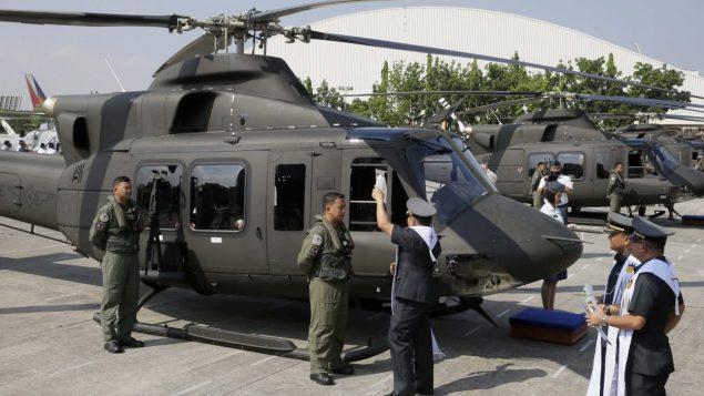 Un aumônier militaire philippin asperge d'eau bénite, en 2015, un des huit appareils alors acquis de Bell Helicopter. Photo : The Associated Press/Bullit Marquez