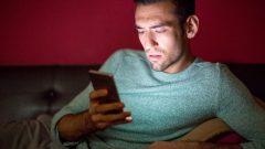 Un homme visiblement préoccupé ou tendu consulte son cellulaire durant la nuit. Photo : Radio-Canada