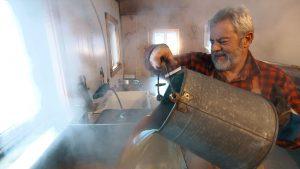 À la cabane du Pic Bois, au Québec, la famille Pollender fabrique le sirop d'érable dans la plus grande tradition. Affairé autour de son évaporateur, André Pollender, le propriétaire de la cabane. Photo : Radio-Canada