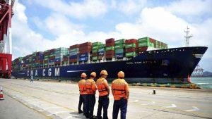Des débardeurs regardent un bateau sur le quai d'un port chinois. Photo : Associated Press/Chinatopix via AP