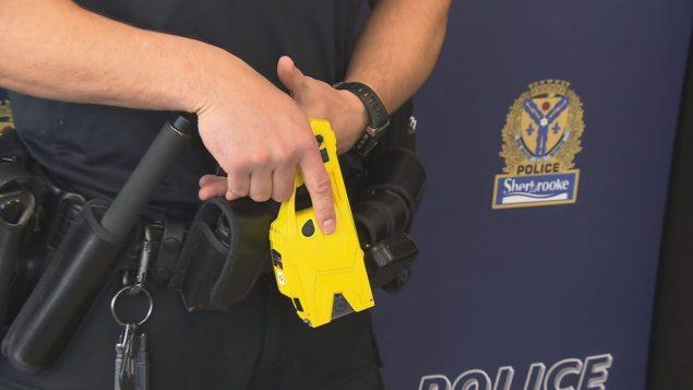 Un pistolets à impulsion électrique dans les mains d'un policier de Sherbrooke près de Montréal. Photo : Radio-Canada