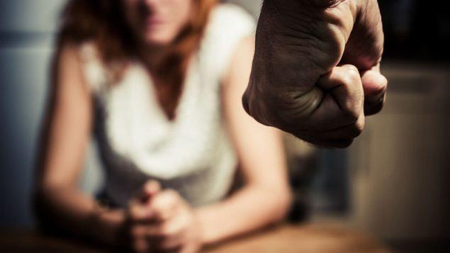 Le poing fermé d'un homme menace une femme.