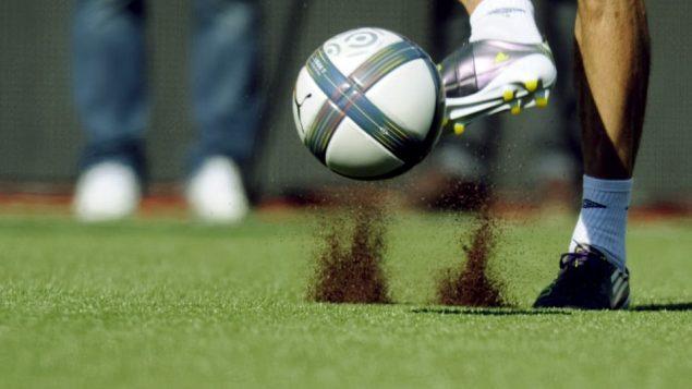 Des particules de caouthouc volent dans les airs lorsqu'un joeur de soccer frappe un ballon.