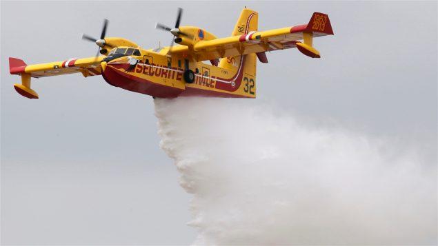 Un avion-amphibie canadair largue de l'eau pour combattre un incendie.