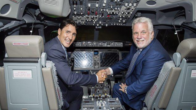 Le pm du Canada, Justin Trudeau, serre la main du pm du Québec, Philippe Couillard, dans un simulateur de vol fabriqué par CAE.