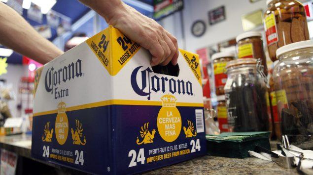 Une caisse de bière de marque Corona au guichte d'un petit marché aux États-Unis.