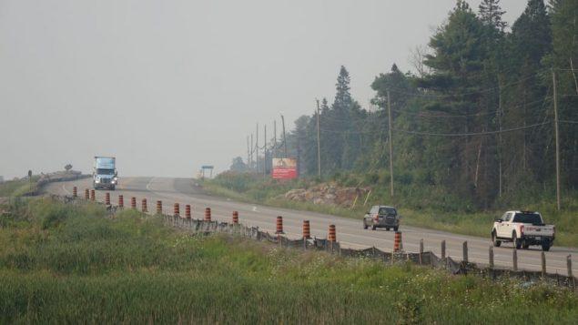 Des voitures roulent sur la route 69 en Ontario sous un couvert de fumée.