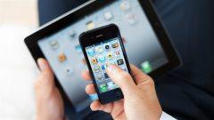 Une personne consulte son téléphone cellulaire et sa tablette numérique