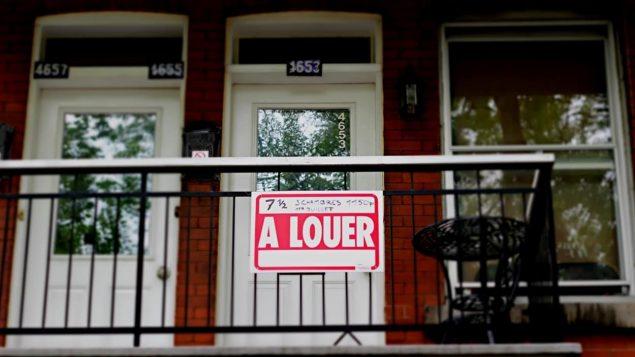 Un enseigne pour pour un appartement à louer au balcon d'un immeuble.