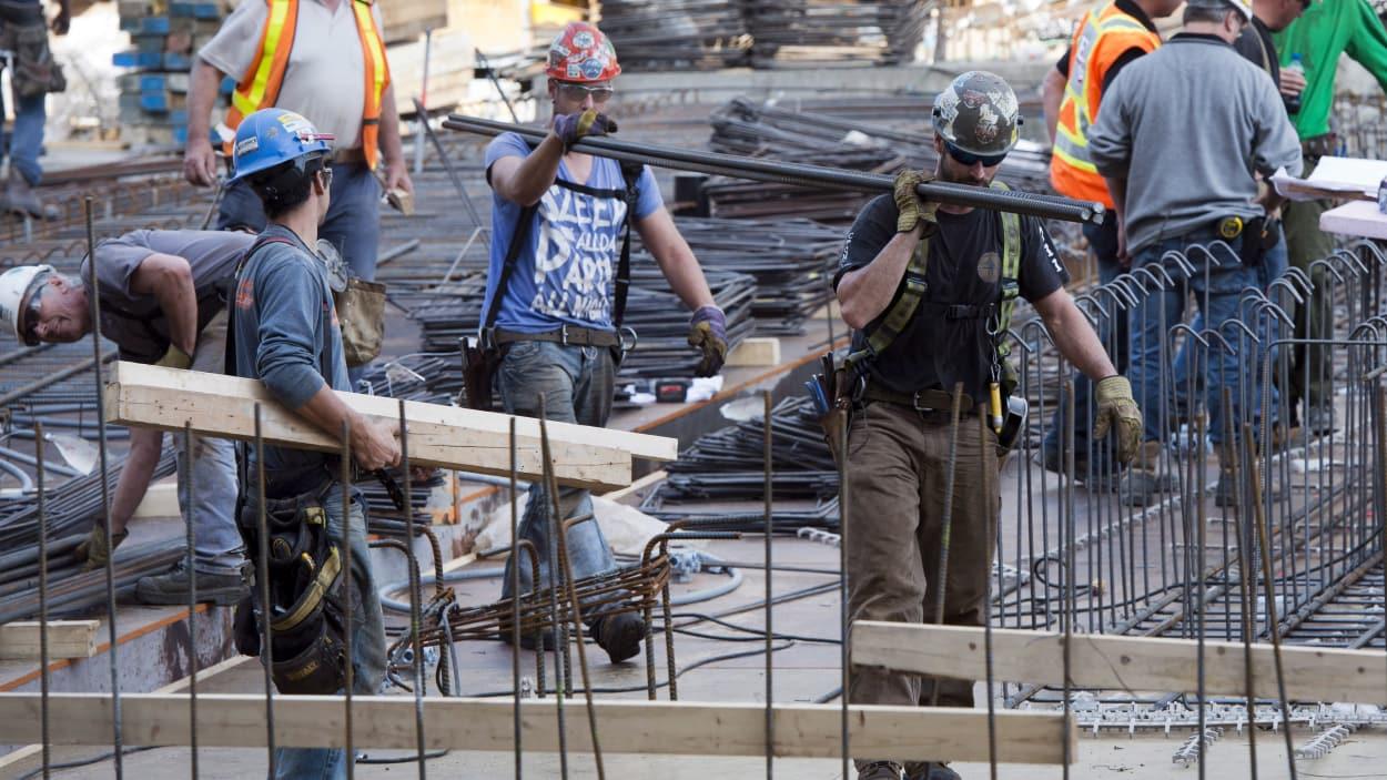 Des hommes transportent du matériel sur un chantier
