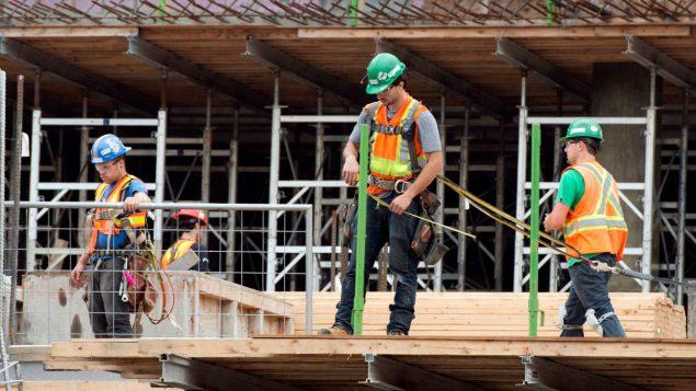 Des travailleurs s'affairent à construire un immeuble à Montréal.