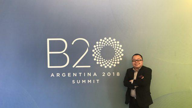 Winston Chan pose devant le logo du B20 en Argentine