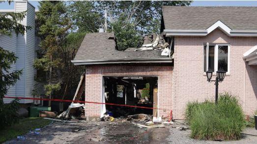L'explosion de la voiture électrique avait soufflé la porte d'un garage résidentiel et causé des dégâts importants vendredi après-midi à L'Île-Bizard, dans l'ouest de Montréal - Radio Canada /  Mathieu Daniel Wagner