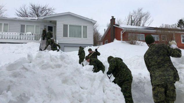 Des soldats canadiens déneigent l'entrée d'une maison dans le quartier Quidi Vidi, à Saint-Jean-de-Terre-Neuve - Radio Canada / Patrick Butler