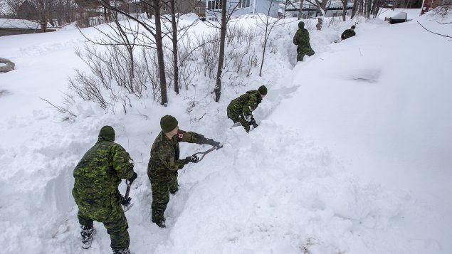 Des soldats des forces armées canadiennes participent au déneigement des entrées des résidences à Saint-Jean, la capitale de Terre-Neuve-et-Labrador - La Presse Canadienne / Andrew Vaughan
