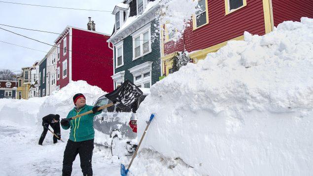Des résidents de Saint-Jean-de-Terre-Neuve déneigent leur voiture le dimanche 20 janvier 2020 - La Presse Canadienne / Andrew Vaughn