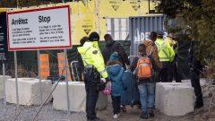 Une famille de demandeurs d'asile arrêtée par des agents de la GRC alors qu'elle traverse la frontière entre le Canada et les États-Unis près de Champlain, dans l'État de New York, le 18 avril 2018. Photo : La Presse Canadienne / Paul Chiasson