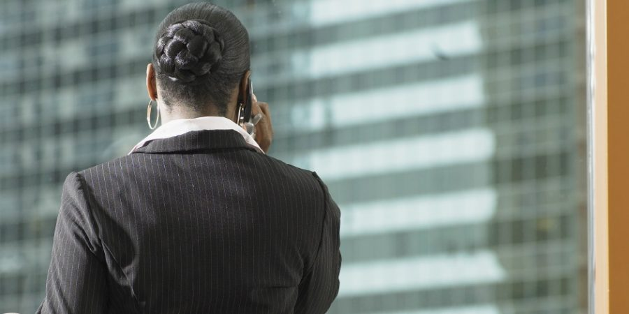 Businesswoman using mobile phone in lobby, rear view