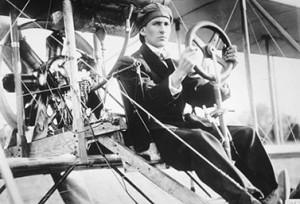 يقود طائرة سلفر دارت في مدينة باديك في نوفا سكوشا, J.A.D. McCurdy  في الثالث والعشرين من شباط/فبراير 1909. إنه أول تحليق على متن طائرة في البلاد. (ارشيف بلدية تورنتو)