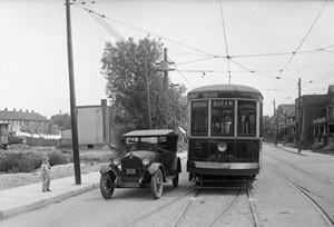 في العشرينيات من القرن الماضي, سيارة وتراموي يتقاسمان خط السير على زاوية شارعي كوين وباي في وسط مدينة تورنتو. )(الأرشيف الوطني, بلدية تورنتو