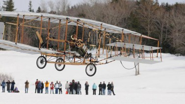A replica of the Silver Dart soars into the sky on the day of the 100th anniversary of the first airplane flight in Canada. (CBC News)